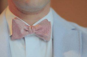 Hombre con modales vistiendo corbata de moño y traje