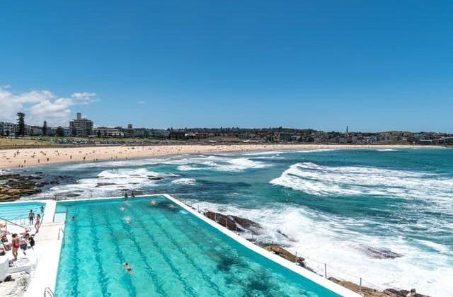 Gente nadando en la piscina Bondi Icebergs y la Playa Bondi en Sydney