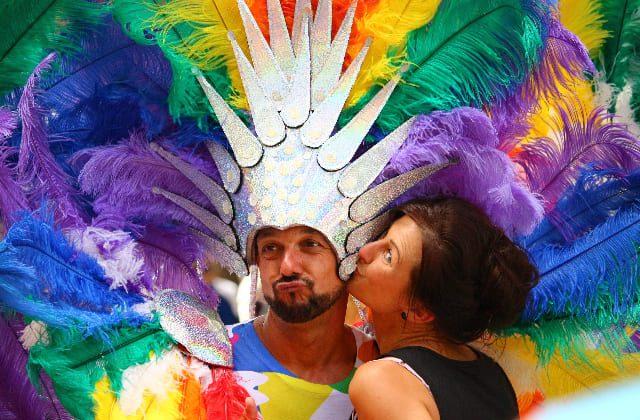 Mujer besando a hombre en la mejilla durante Mardi Gras en Sydney