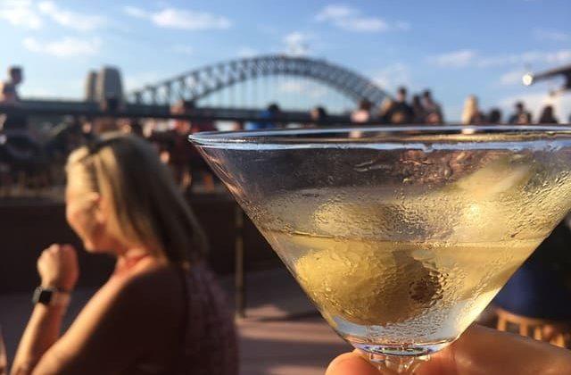 Persona tomando un martini en un bar de Sydney con vista a la Casa de la Ópera
