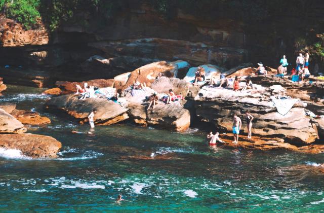 Gente asoleándose sobre las rocas en Gordons Bay, Sydney