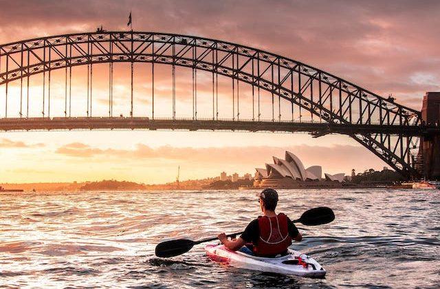Persona haciendo kayak en la bahía de Sydney con vista hacia la Casa de la Ópera y el Puente de la Bahía