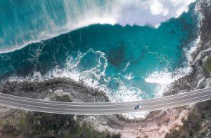 Vista aérea del puente con un coche en medio y una ola rompiendo