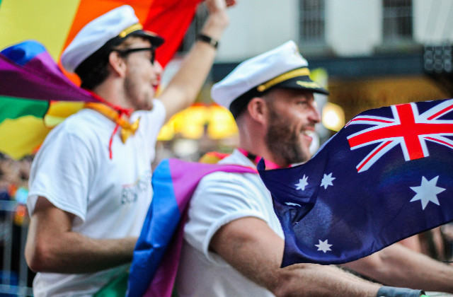 Dos hombres en una motocicleta conduciendo durante el desfile LGBT en Australia