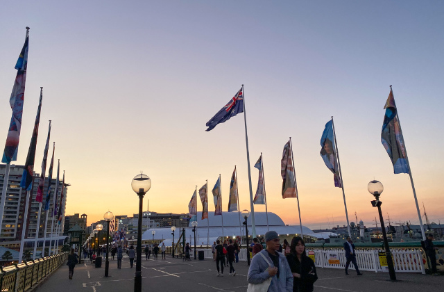 Pareja caminando por el puente de Darling Harbour después de aplicar para la visa de pareja en Australia